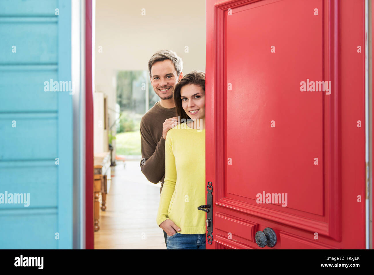 A grey hair man with beard and a woman are opening the red door of their wooden house to welcome some guests. The - Stock Image