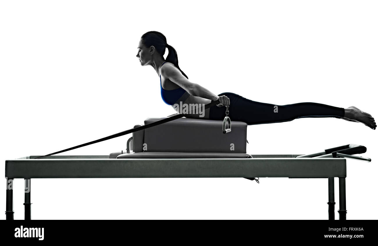 one caucasian woman exercising pilates reformer exercises fitness in silhouette isolated on white backgound - Stock Image