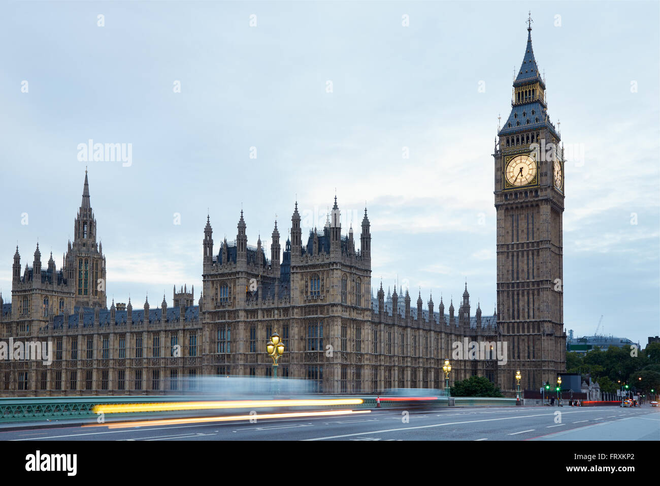 Big Ben and bridge in the early morning, car passing lights in London - Stock Image