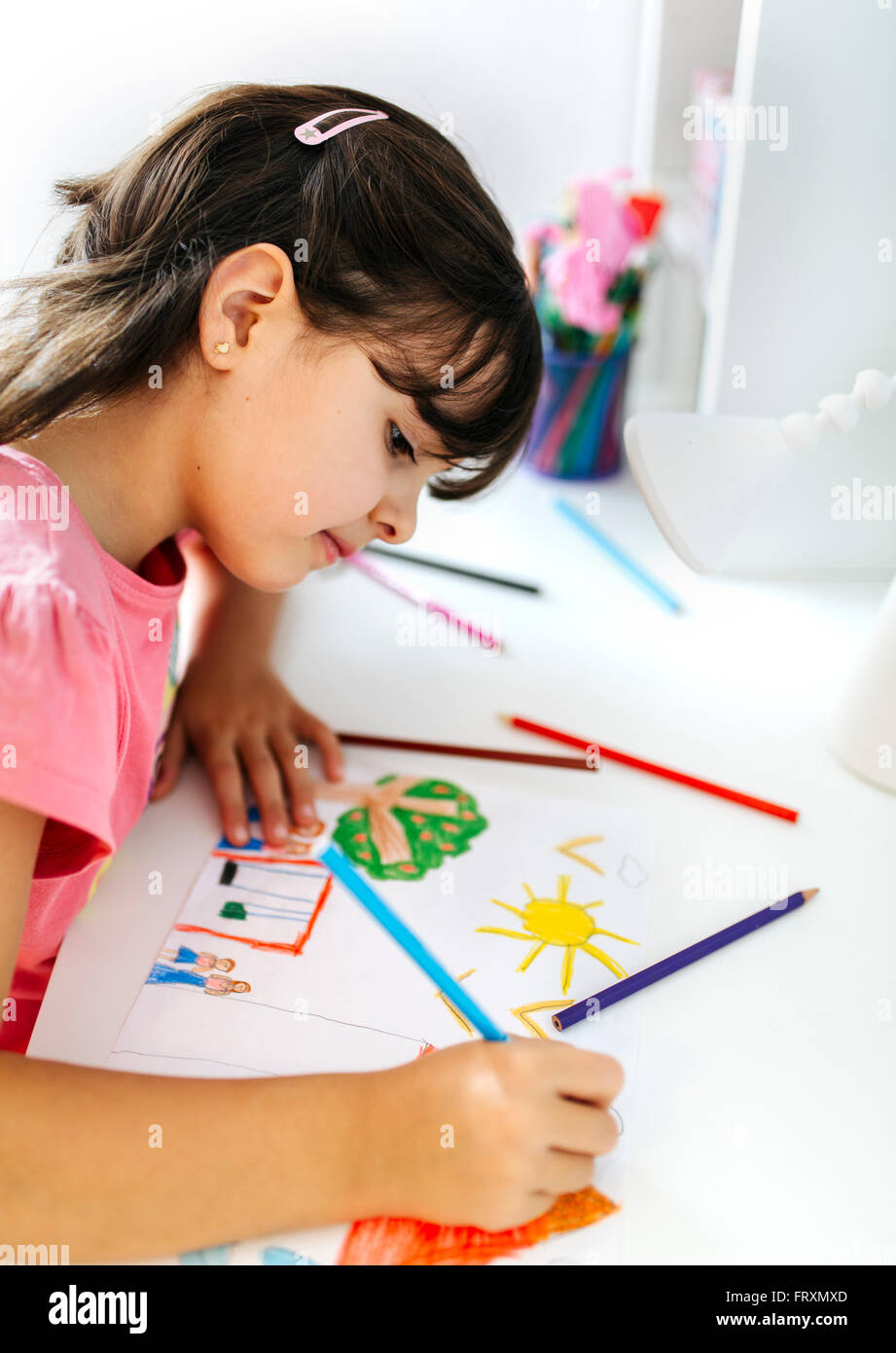 Little girl drawing on his desk at home - Stock Image