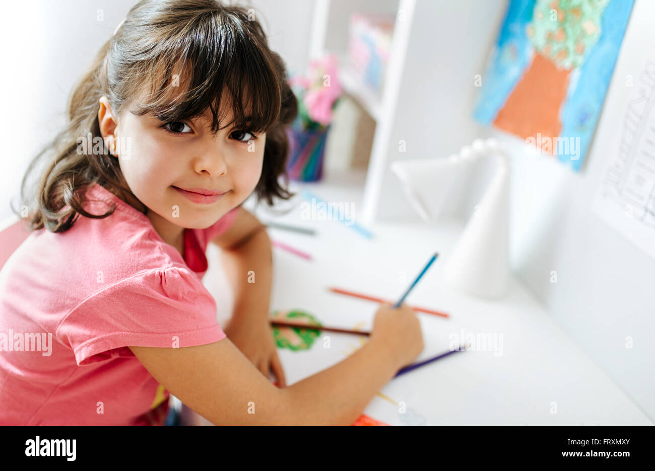 Portrait of little girl drawing on his desk at home - Stock Image