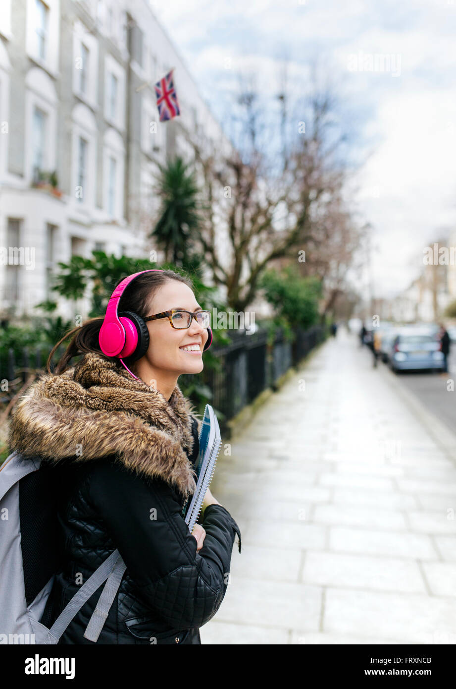 London, student girl with headphone and writing pad - Stock Image