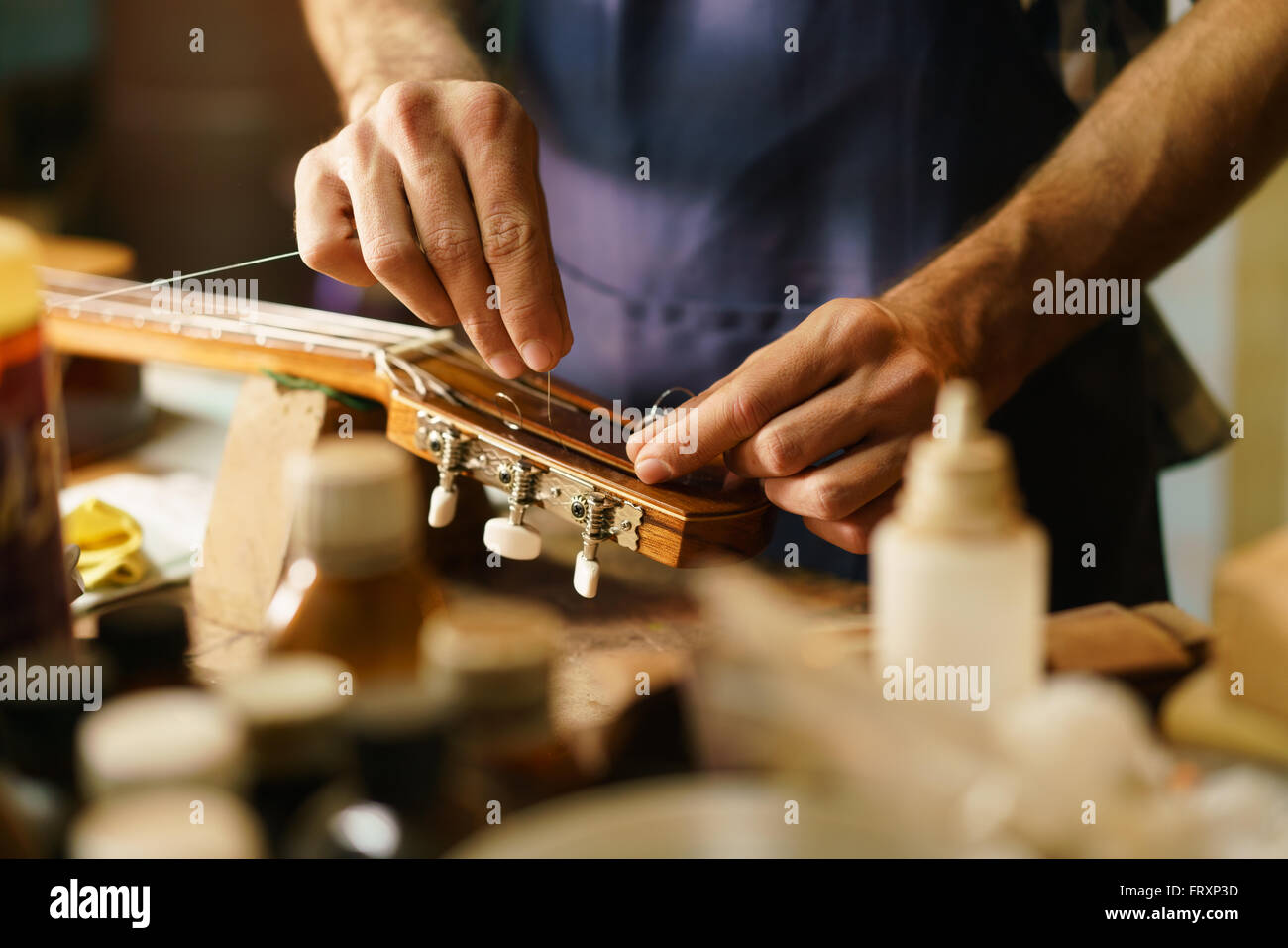 Lute maker shop and classic music instruments: young adult artisan fixing old classic guitar adding a cord and tuning - Stock Image