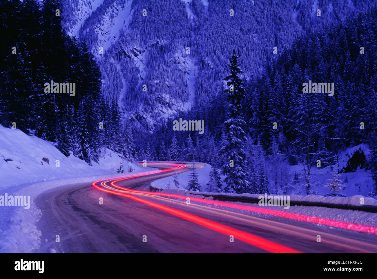 Streaking Car Tail Lights on a Road in Winter, Banff National Park, Alberta, Canada Stock Photo