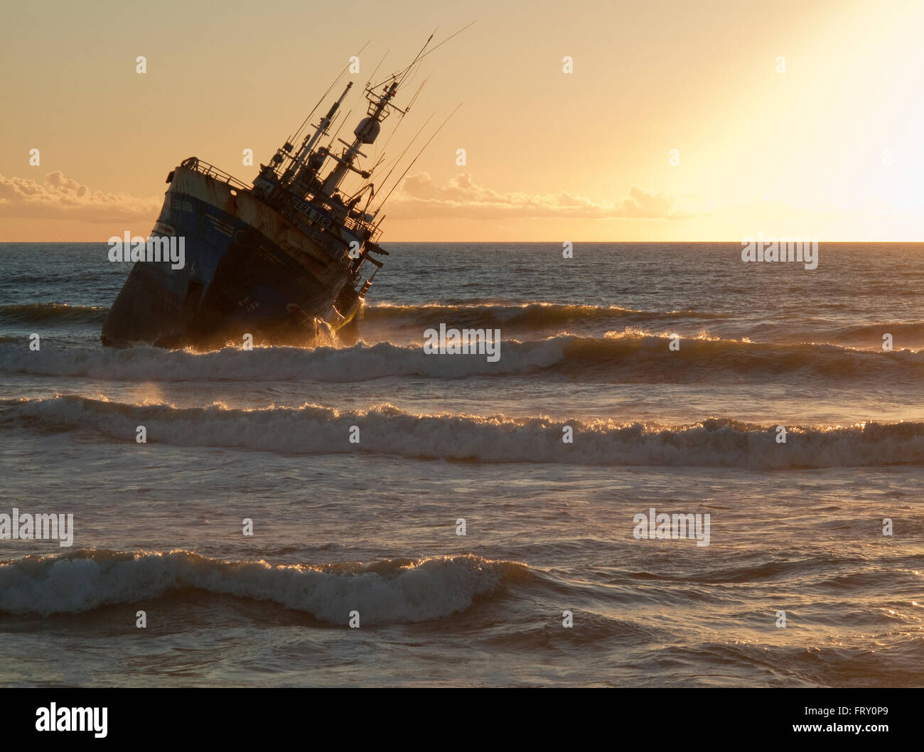Shipwreck at sunset at Laayoune Plage, Western Sahara, Southwest Morocco - Stock Image