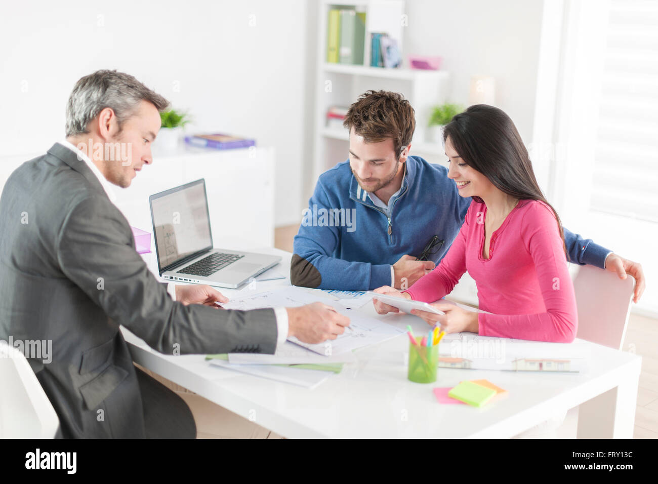 real-estate agent shows a build project  to a young couple Stock Photo