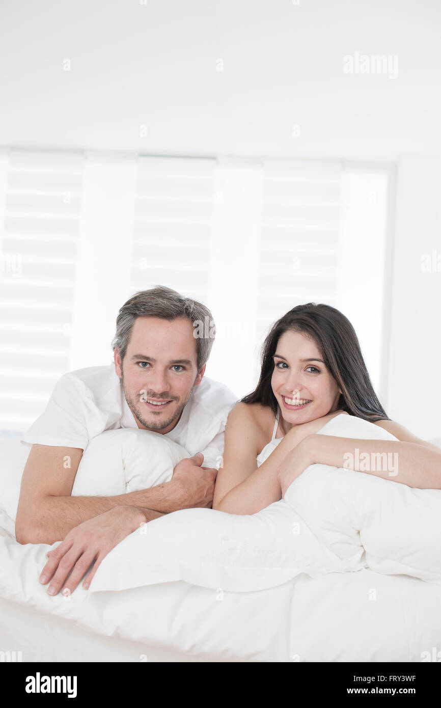 Young couple lying together in bed in the bedroom - Stock Image