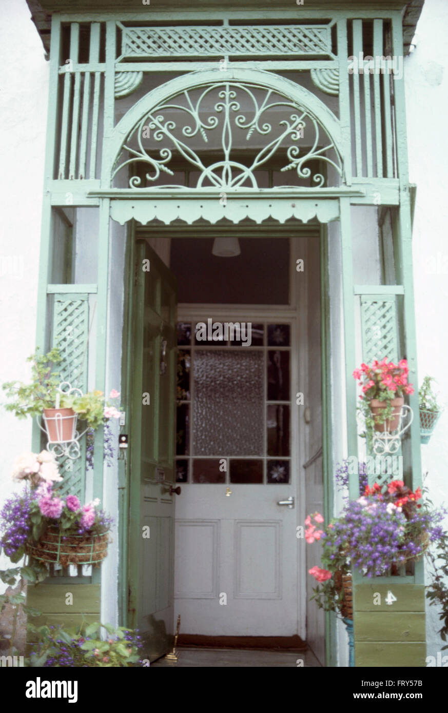 Hanging Baskets On Ornate Porch On A Half Glazed Stained