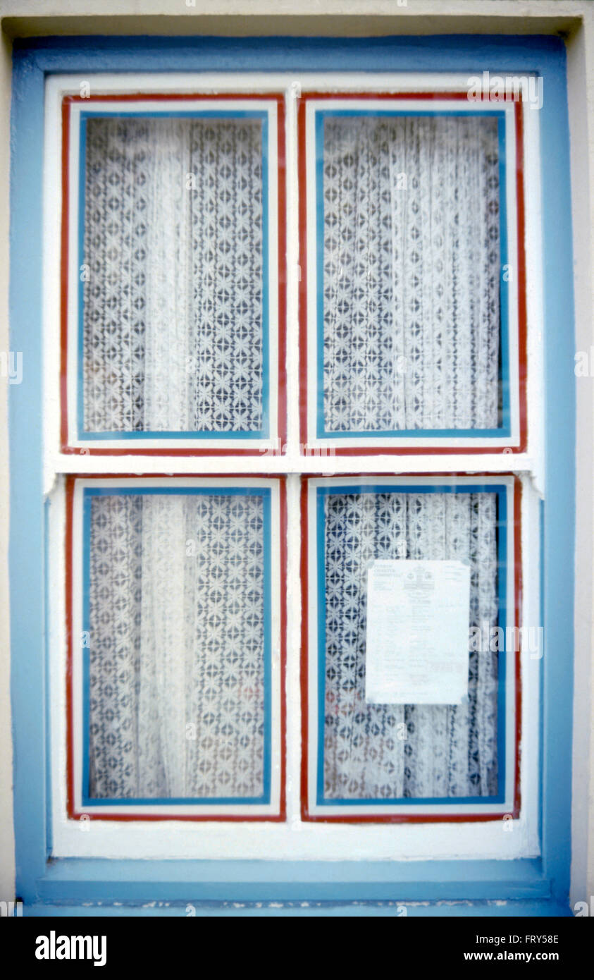 Close-up of a red white and blue painted window with net curtains - Stock Image