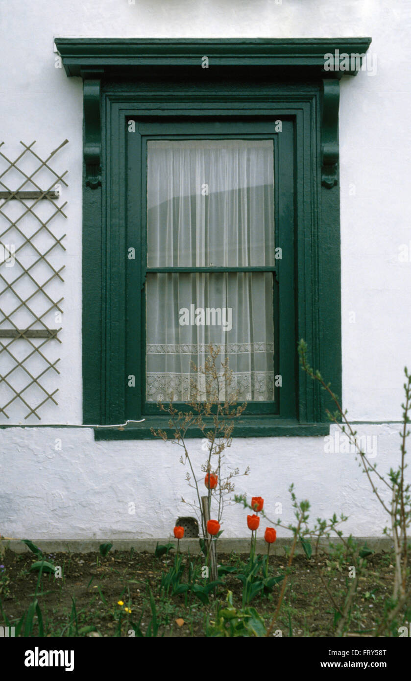 Close-up of a white cottage with a black window and net curtains - Stock Image