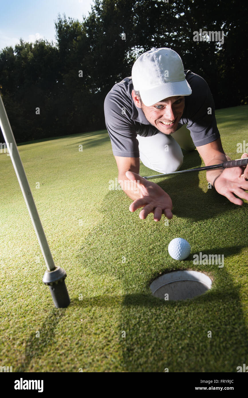 Golfer stunned because he missed his last swing Handsome golfer lying down on the green, hands on the ground Wide - Stock Image