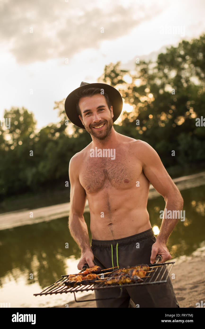 A smiling man with hat and beard is holding the barbecue grill. He is  standing shirtless in the sand at the beach with his swimsuit. 377fe467f14