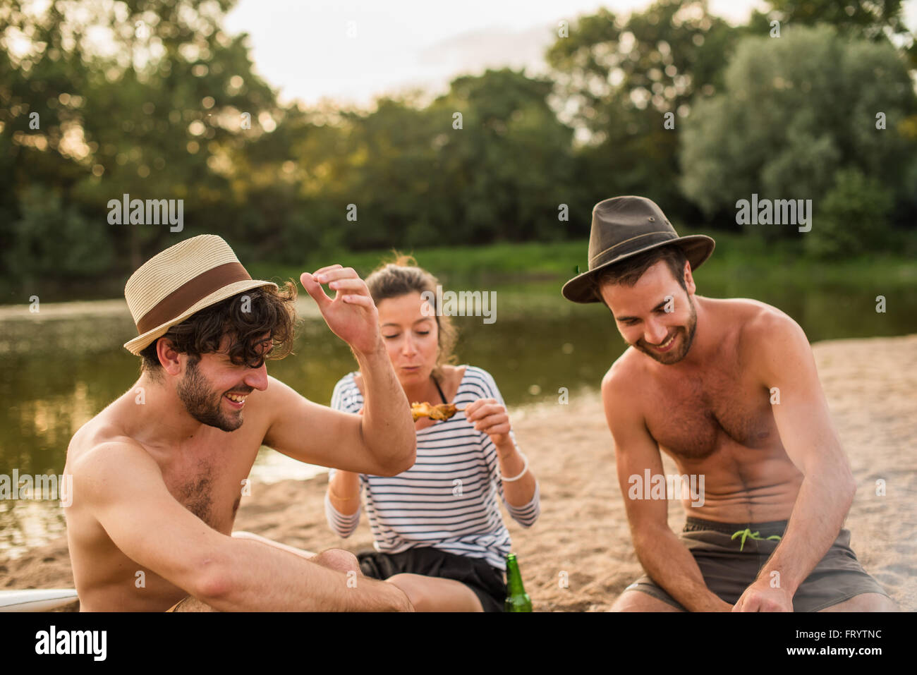 Evening at the beach. The barbecue is done, everybody is sitting in the sand, smiling and eating his chicken kebabs. - Stock Image