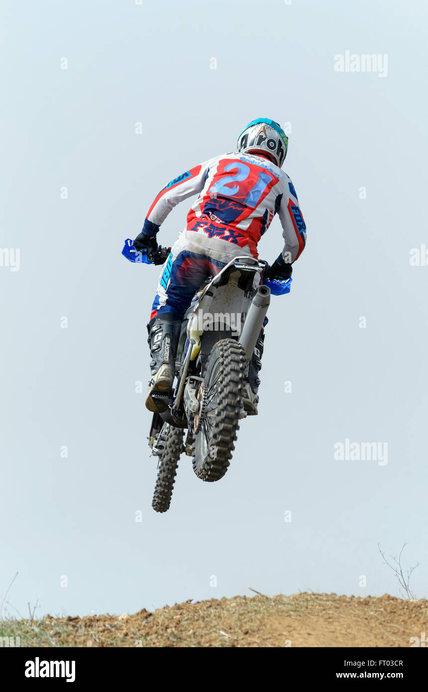 Spain cross country championship. Back view of motorcyclist when he is jumping with his motocross motorbike, in - Stock Image