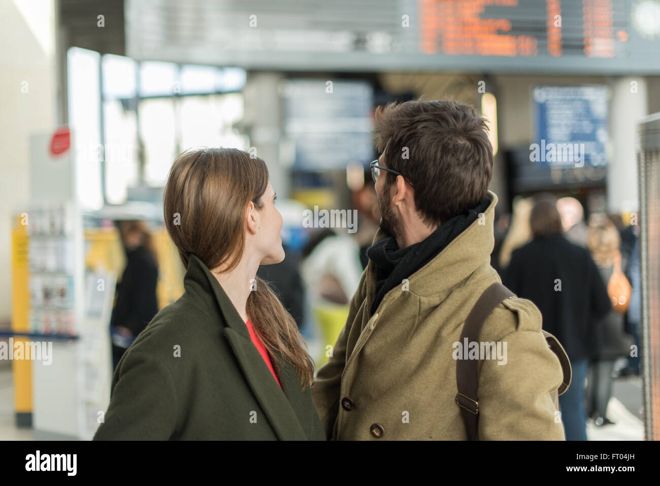 young couple looking at departure announcements in a train station - Stock Image