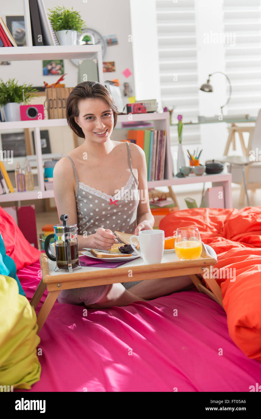 looking at camera, a smiling young woman in nightwear taking a breakfast on her colorful bed, her interior is bright - Stock Image