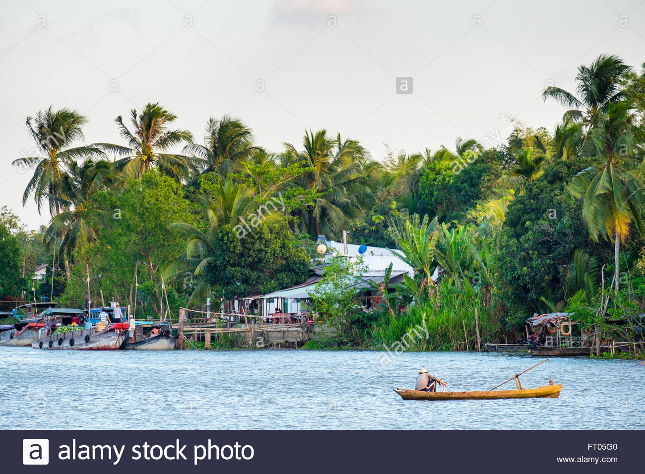 A man fishing in a small boat on the Can Tho River, a branch of the Mekong River, Can Tho, Mekong Delta, Vietnam - Stock Image