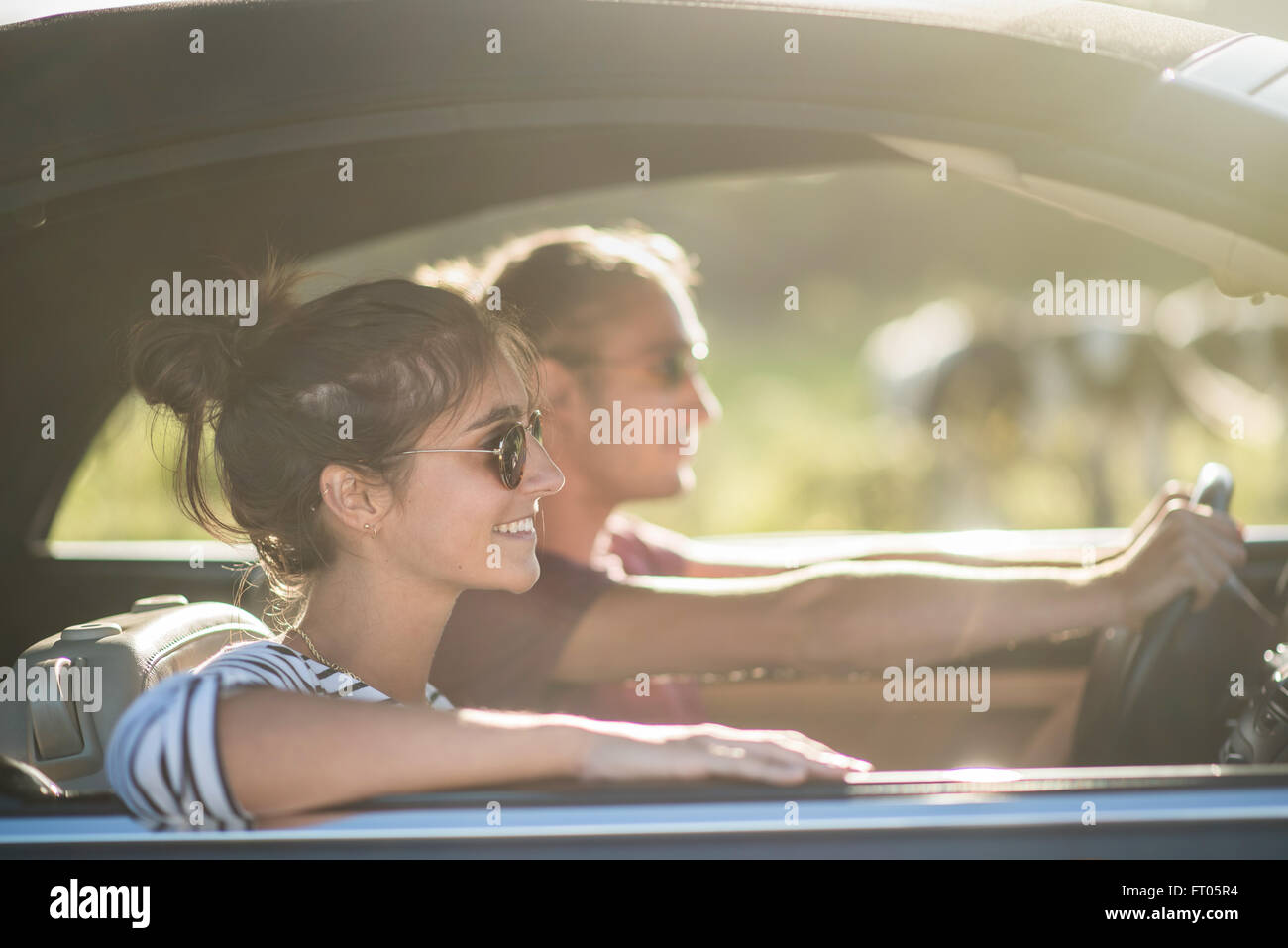 Young couple in his car, happy to drive on a country road, focus on the woman. There are some blurred cows at the - Stock Image