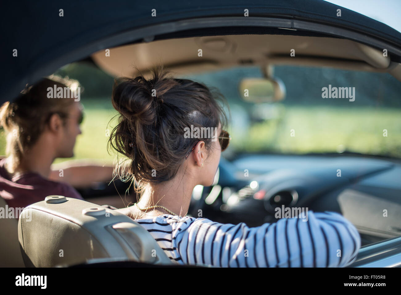 Young couple in his car, happy to drive on a country road, focus on the woman. Shot with flare. There are some blurred - Stock Image