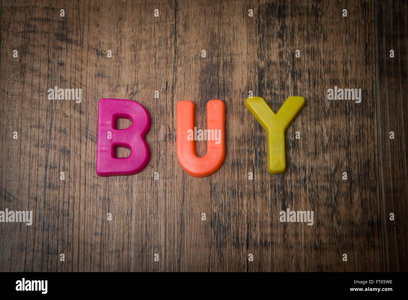 fridge magnet coloured letters spelling out buy - Stock Image