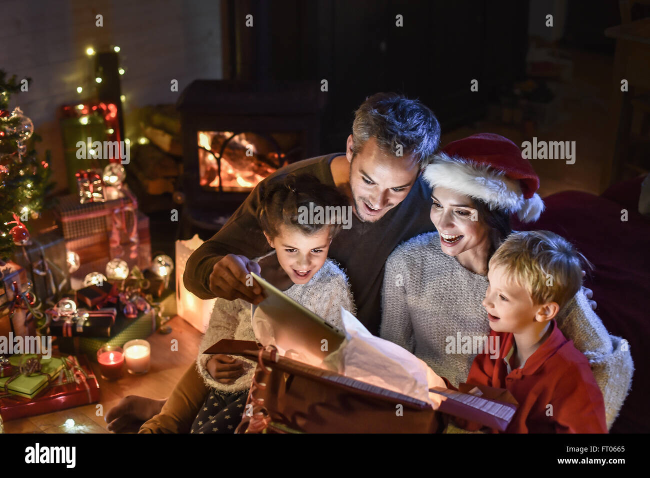 8dfa3bac21269 happy family finds a digital tablet in a gift on the Christmas night, near  the wood stove and lit Christmas tree in their living room, the mother  wears a ...