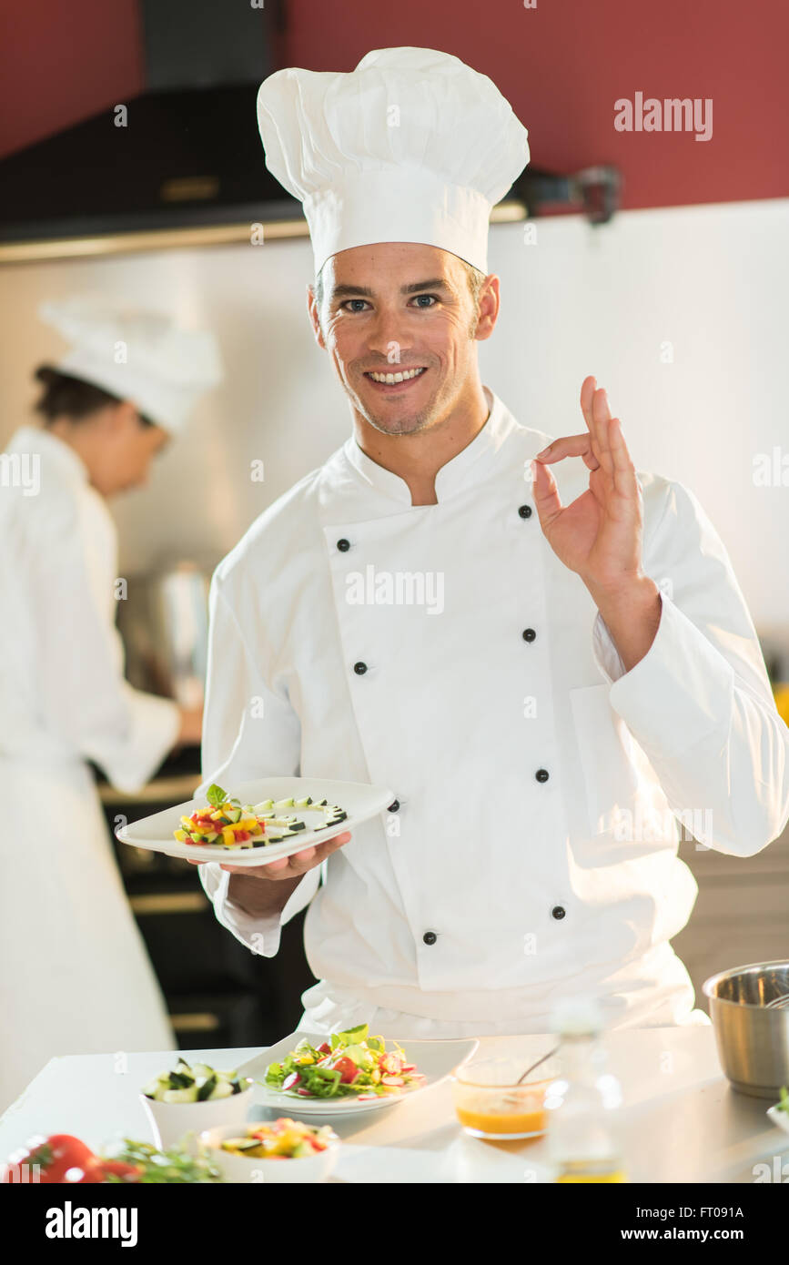 A man chef in his fifties is standing in a professional kitchen ...