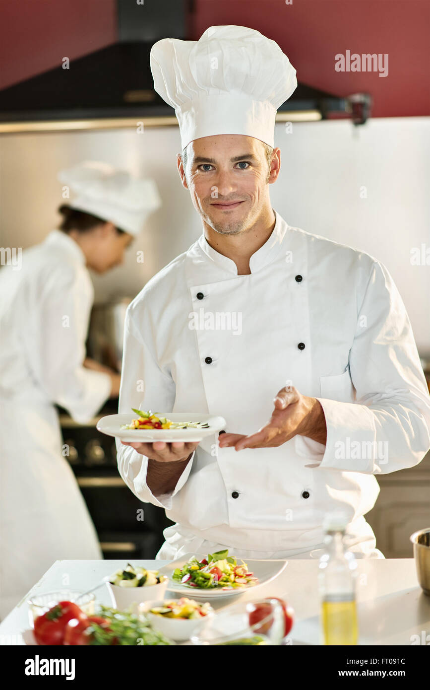 A man cook chef is standing in a professional kitchen presenting a ...