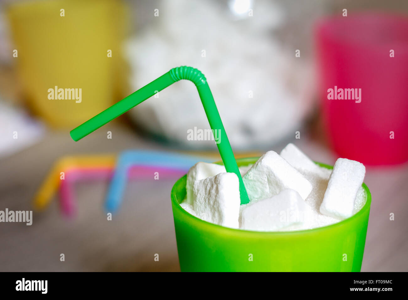 Closeup of green plastic glass with straw full of sugar and sugar cubes. Concept image for too much sugar in sodas - Stock Image