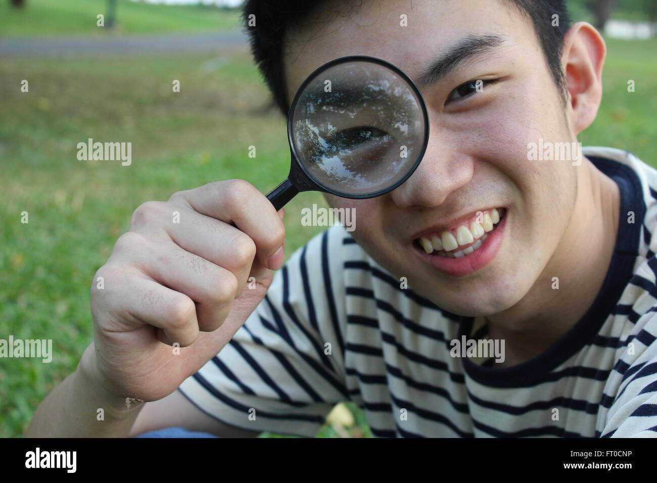 Young man with magnify glass - Stock Image