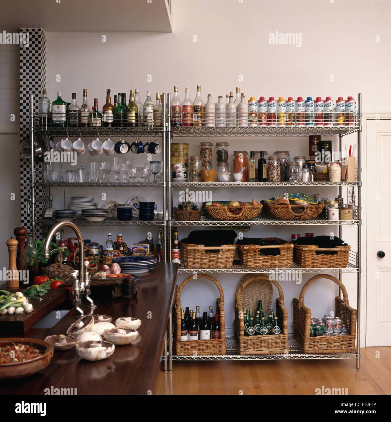 Storage Baskets And Rows Of Bottles On Stainless Steel Storage Shelves In  Modern Kitchen