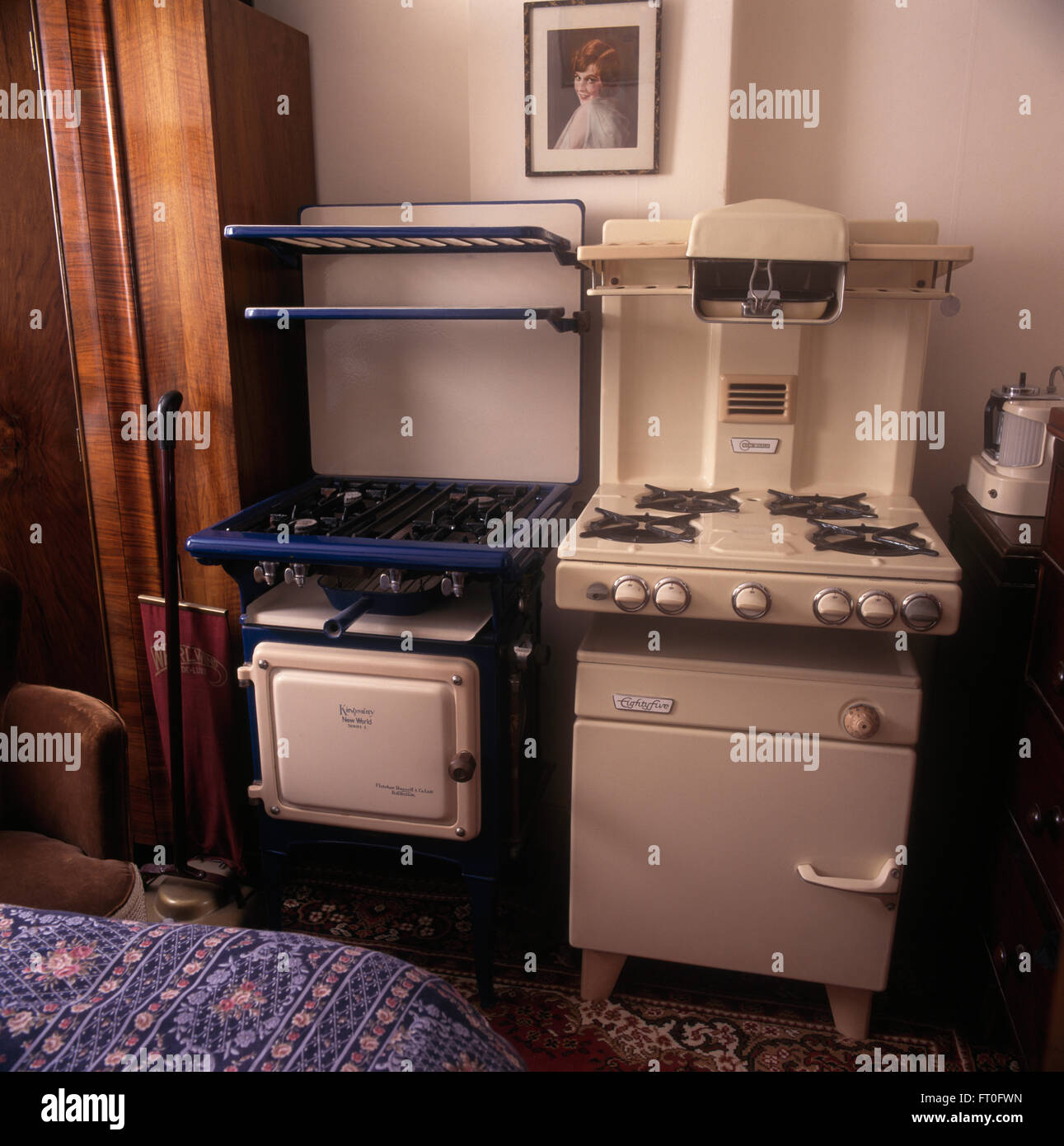 Collection of vintage gas cookers in fifties bedroom - Stock Image