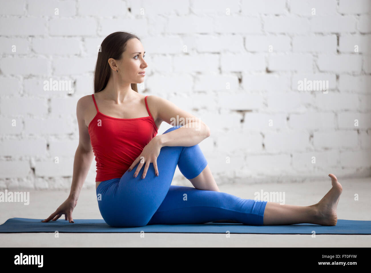 Portrait of beautiful young woman in bright colorful sportswear working out indoors. Girl sitting in half lord of - Stock Image