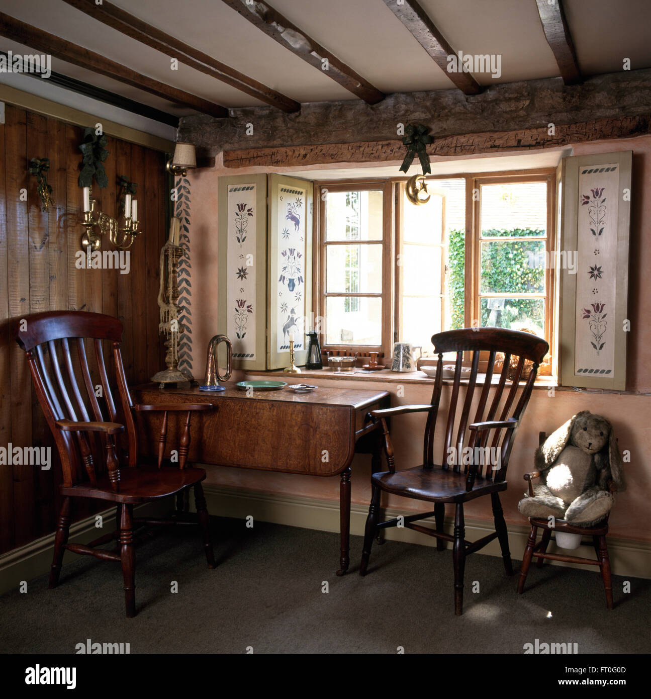 Antique Windsor chairs and old table below window with stenciled shutters  in panelled cottage dining room - Antique Windsor Chairs And Old Table Below Window With Stenciled