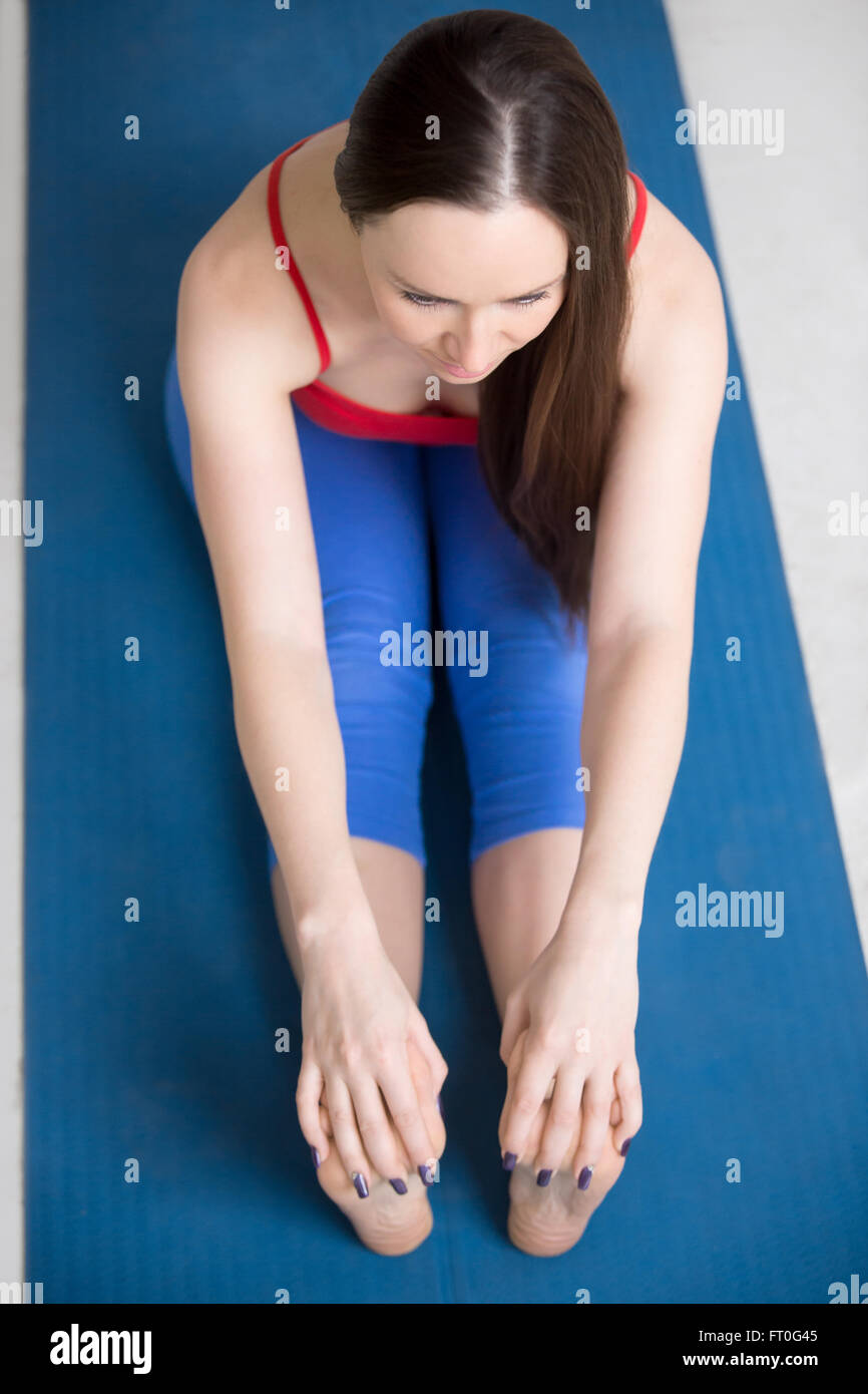 Beautiful young woman in bright colorful sportswear working out indoors on blue mat. Girl sitting in Paschimottanasana - Stock Image