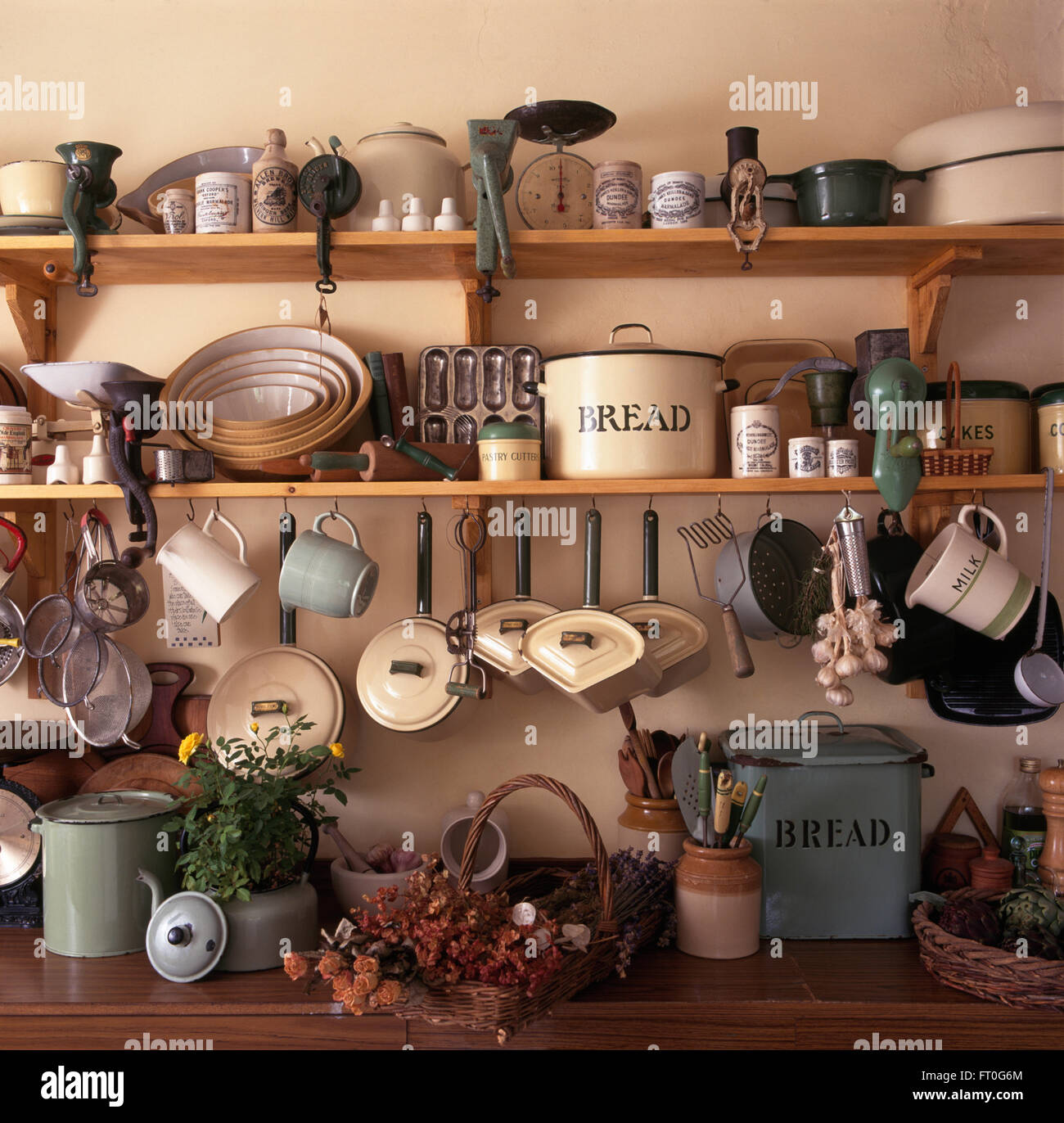 Collection of forties enamelware with pans and bread bins and earthenware vintage bowls on kitchen shelves - Stock Image