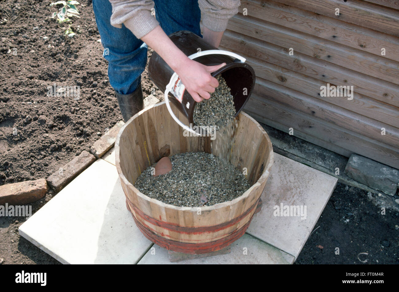 Putting Grit In Its Place >> Close Up Of A Gardener Putting Grit Into A Wooden Barrel Before