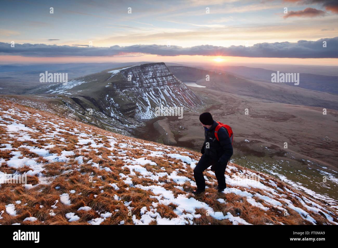 Hillwalker climbing The Black Mountain at sunset. Brecon Beacons National Park. Carmarthenshire. Wales. UK. - Stock Image