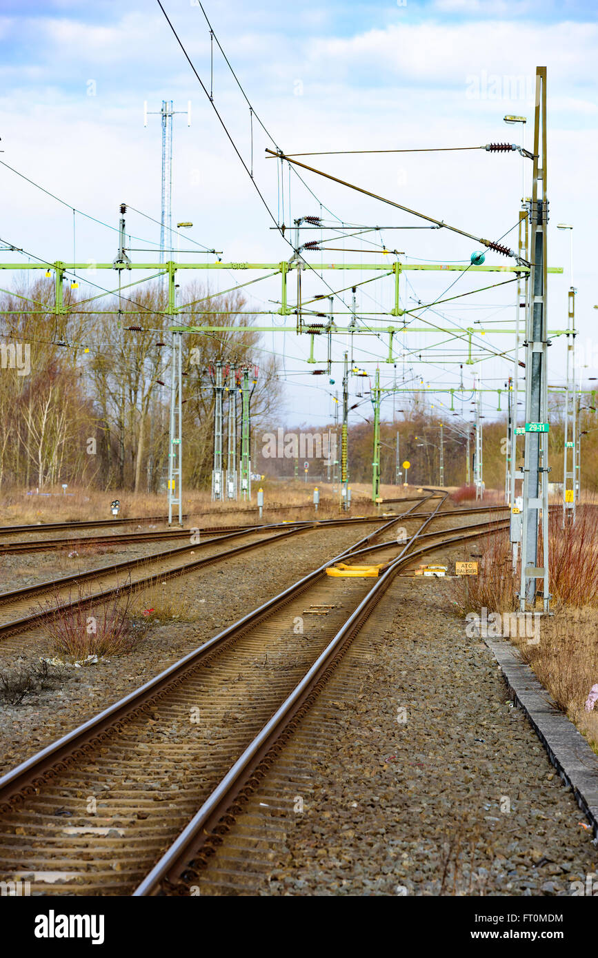 empty railroad track with som train switches and electrical wires leading  off into the distance  small atc balise in the track
