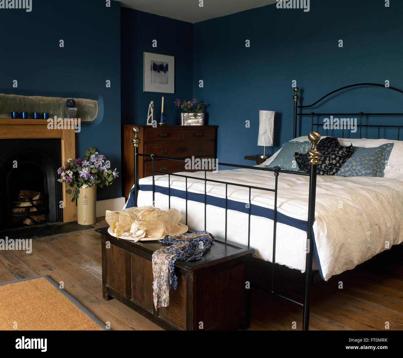 Picture of: Black Wrought Iron Bed With White Duvet In A Blue Bedroom With A Hat Stock Photo Alamy