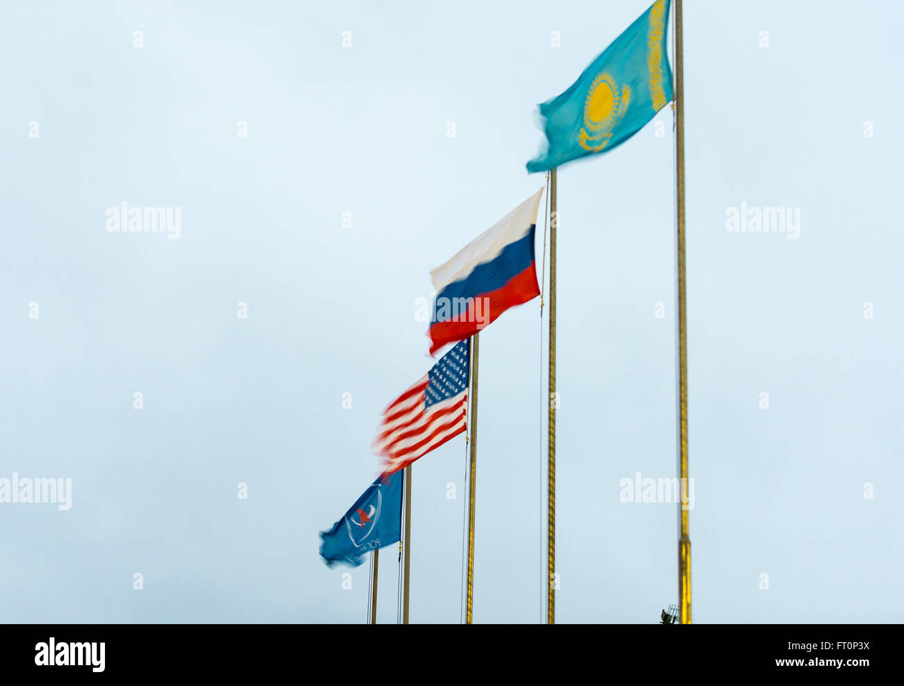 Flags of the U.S., Russia, Roscosmos, and Kazakhstan are seen blowing in the high winds that delayed operations - Stock Image