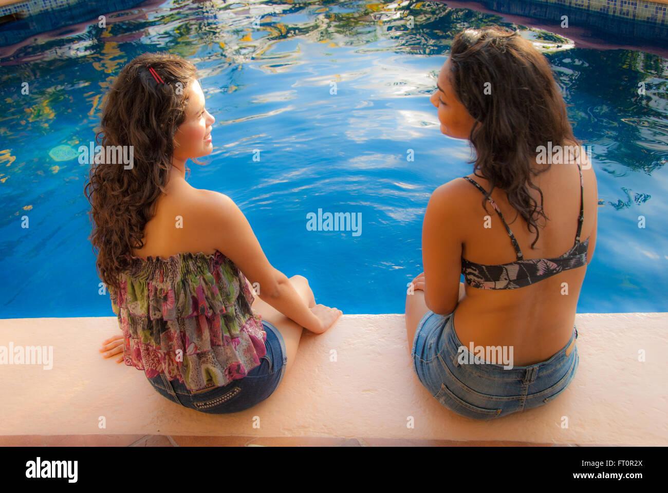 2 young Hispanic women sit by swimming pool, Puerto Vallarta, Mexico  #613PV - Stock Image
