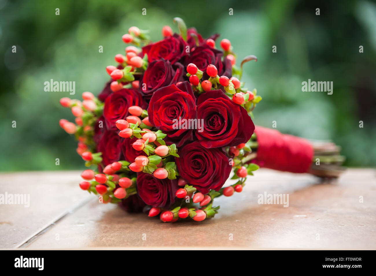 Wedding Bouquet Of Red Roses And Hypericum Tied With A Red Ribbon