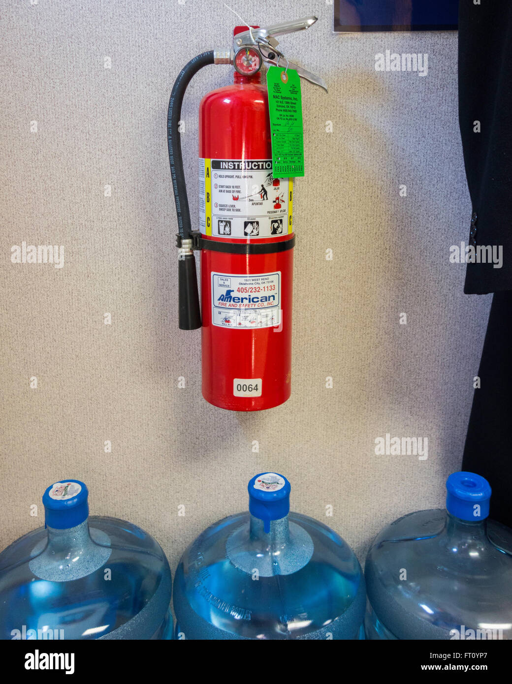 A mandatory fire extinguisher hangs on a wall over 3 five gallon water bottles in a storage area of a business. - Stock Image