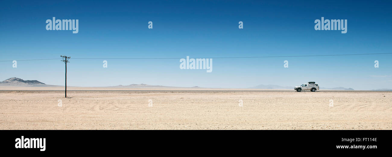 4x4 vehicle in the desert and electricity pylon close to Luderitz, Namibia, Africa - Stock Image