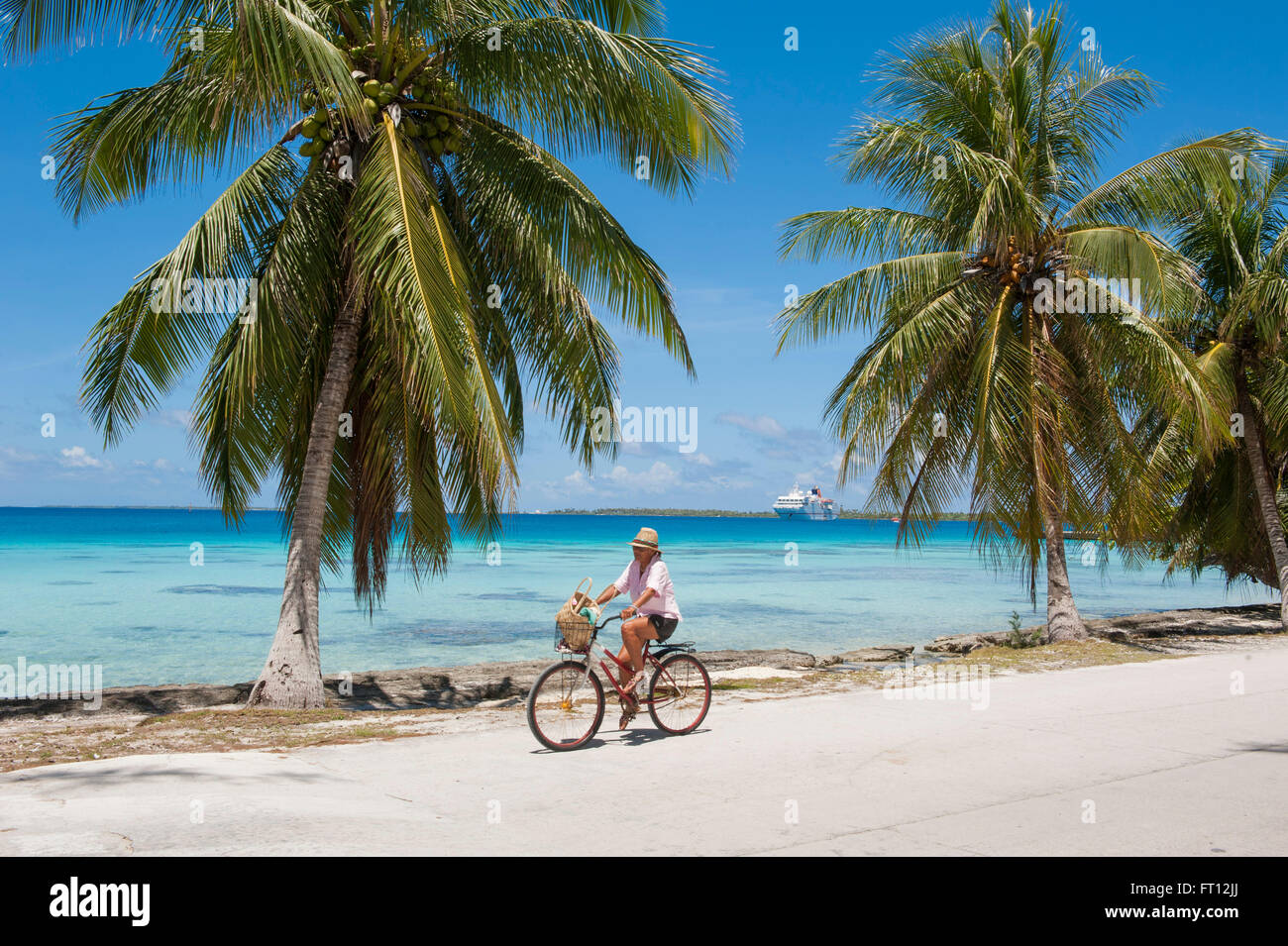 Man riding his bicycle along a road with palm trees, expedition cruise ship MS Hanseatic Hapag-Lloyd Cruises at - Stock Image