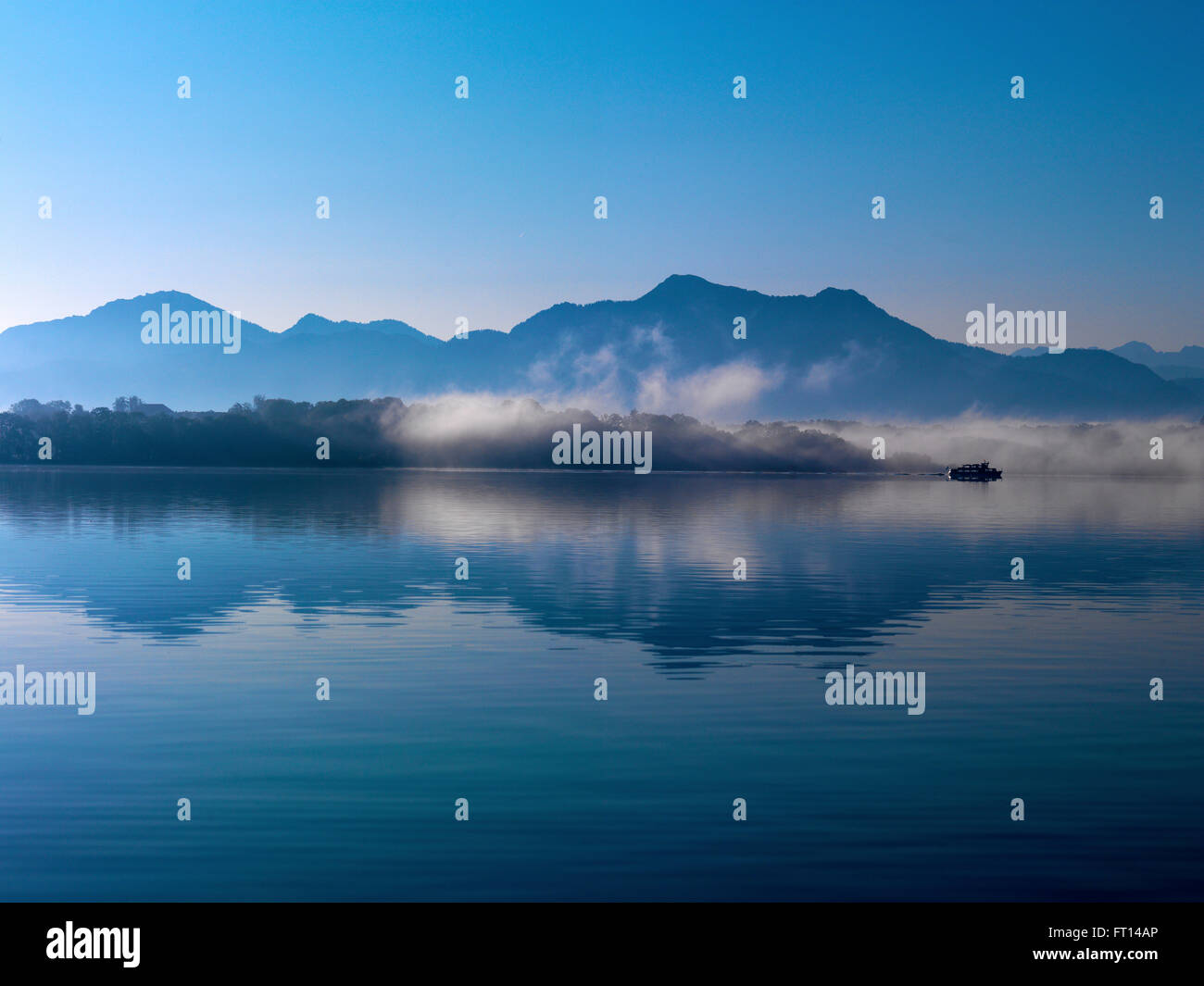 Herreninsel and mountains Hochfelln and Hochgern in morning fog, lake Chiemsee, Bavaria, Germany - Stock Image