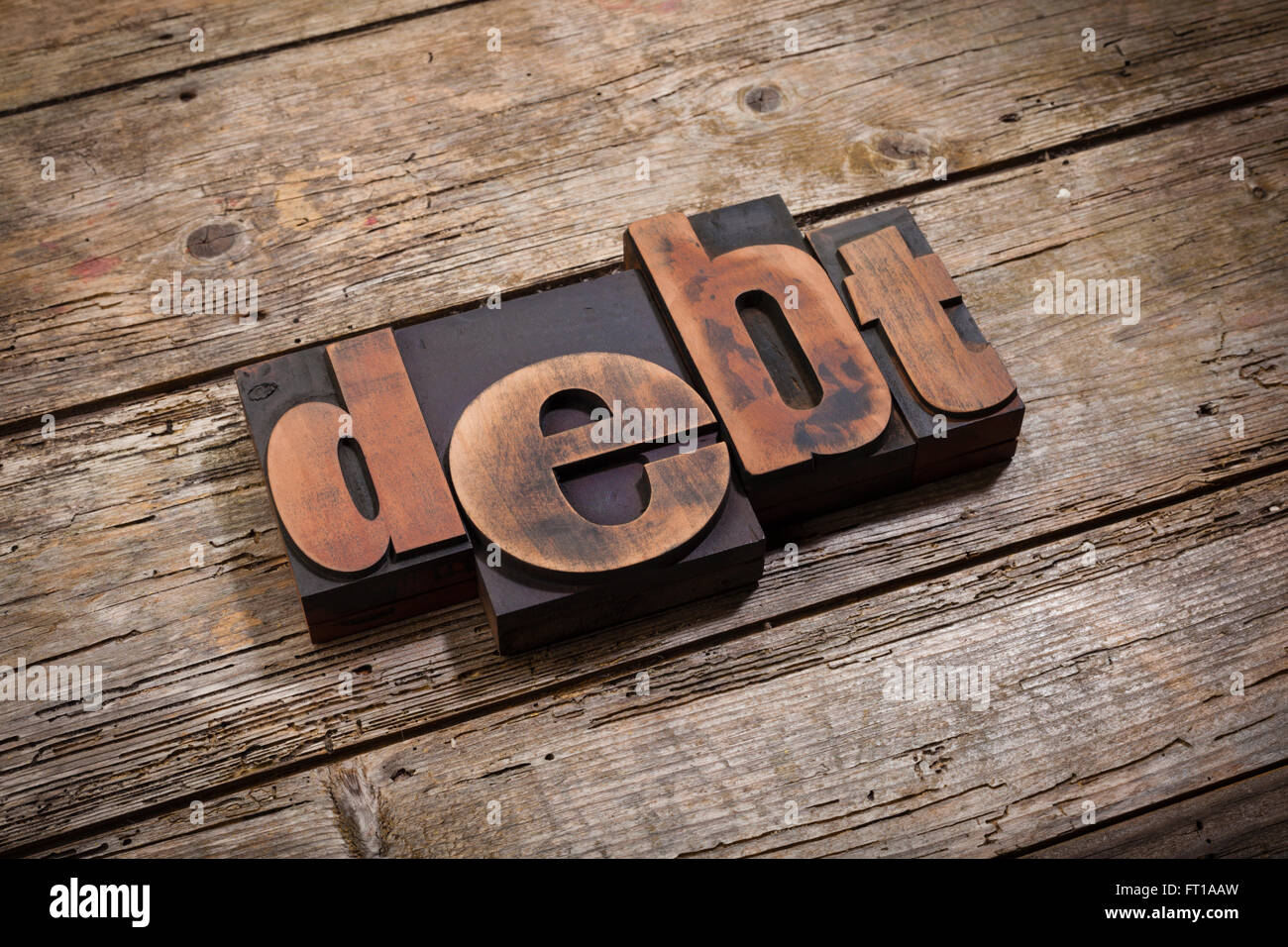 Debt, word written with vintage letterpress printing blocks on rustic wooden background, angled view - Stock Image