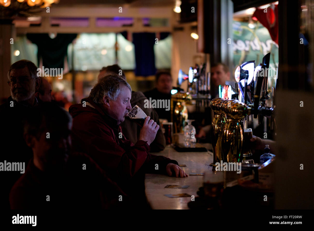Middle aged man drinking a pint of beer alone in a pub - Stock Image