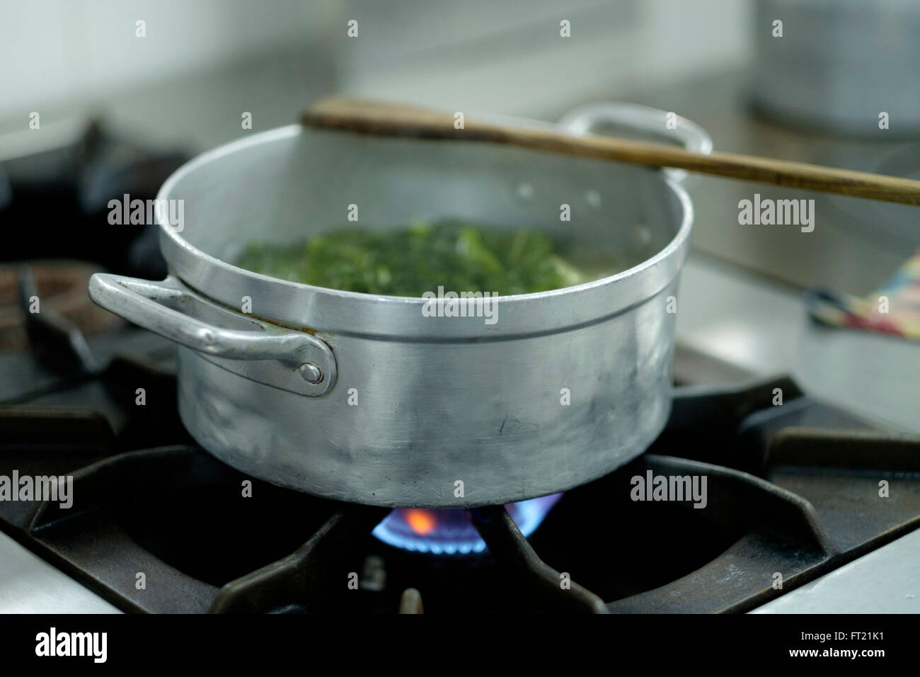 Vegetables being cooked in a metal pan on a stove - Stock Image