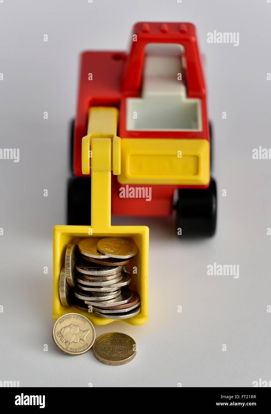A toy digger carrying coins Stock Photo